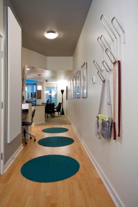Zielone, owalne dywany w korytarzu.